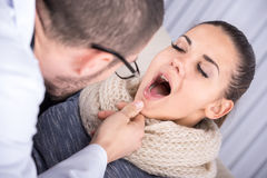 Disease. Doctor consulting a young woman, sore throat concept Stock Photography