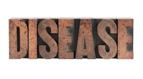 Disease in letterpress wood type. The word 'disease' in ink-stained wood letters isolated on white Royalty Free Stock Photo