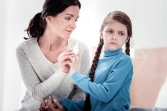 Portrait of careful mother and fussy child. Disease. Portrait of young careful mother holding nasal drops while her daughter resisting being cured royalty free stock photo