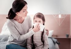 Young mother taking care of her ill child stock photography