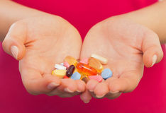 Disease prevention. Close up of a young woman hand with pills Stock Images