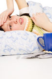 diseased beautiful girl lying in bed Stock Photography