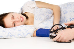The diseased beautiful girl lying on the bed, and measure the pr Stock Image