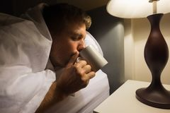 Diseased caucasian mature man drink the water on the bed closeup at night. He has hangover after party or flu royalty free stock photos