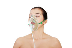 Diseased female patient wearing a oxygen mask royalty free stock image