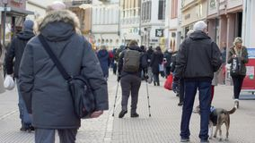 Diseased female tourist with leg handicapped using crutches walking with backpack down street among crowd of people in stock video footage