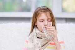 Diseased girl drinks water. Little diseased girl drinks water stock images