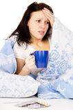 The diseased girl lying on the bed, and drink medicine Royalty Free Stock Images