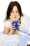 The diseased girl lying in bed, drinking tea Stock Photos