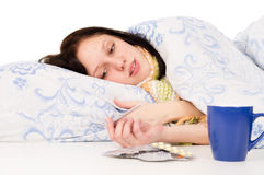 The diseased girl lying in bed, drinking tea Stock Images