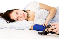 The diseased girl lying on the bed, and measure the pressure Stock Photos