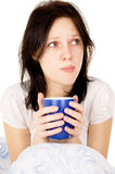 The diseased girl sitting on the bed and drink medicine Stock Images