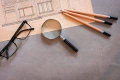 Disegnando con i vetri, le matite e la lente d'ingrandimento sulla tavola concreta immagine stock libera da diritti