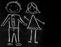 Disegnando con il gesso sul ragazzo e sulla ragazza neri del fondo Fotografia Stock