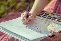 Disegnando e spazzola nelle mani della ragazza Fotografie Stock Libere da Diritti
