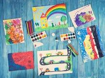 Disegni del bambino con gli accessori di tiraggio su fondo di legno blu immagini stock