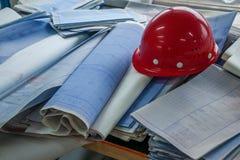 Disegni di costruzione dell'ufficio del sito del cantiere dell'alloggio sui caschi Immagini Stock