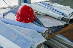 Disegni di costruzione dell'ufficio del sito del cantiere dell'alloggio sui caschi Fotografia Stock