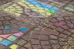 Disegni di gesso di Chlidren's sulla pavimentazione/asfalto fotografie stock