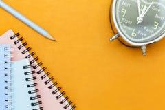 disegni a matita con il taccuino e la sveglia su fondo di carta arancio Fotografie Stock Libere da Diritti