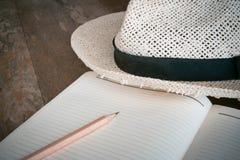 Disegni a matita il cappello bianco del taccuino su vecchio legno table1 Immagini Stock Libere da Diritti