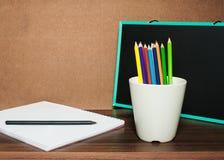 Disegni a matita variopinto in tazza bianca con il blocco note ed il bordo nero Fotografia Stock