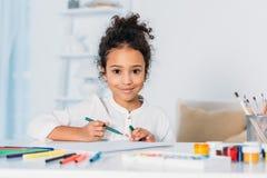 disegno afroamericano adorabile del bambino con le penne del feltro ed esaminare macchina fotografica fotografia stock