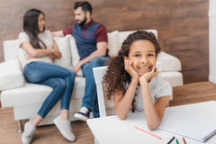 Disegno afroamericano della ragazza con le matite variopinte mentre i suoi genitori che si siedono dietro Fotografia Stock Libera da Diritti