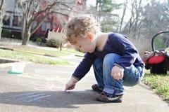 Disegno del bambino con il gesso fuori Fotografia Stock