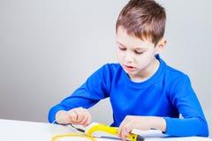 Disegno del bambino con la penna di stampa 3d Creativo, tecnologia, svago, concetto di istruzione Immagine Stock