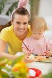 Disegno del bambino e della madre sulle uova di Pasqua Fotografie Stock Libere da Diritti