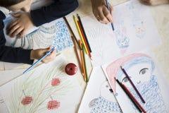 Disegno del ragazzo con i pastelli alla tavola Fotografia Stock Libera da Diritti