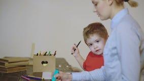 Disegno del ragazzo e della madre del bambino con le matite variopinte Ragazzo con la pittura della madre isolata su fondo bianco video d archivio