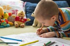 Disegno del ragazzo del piccolo bambino con le matite di colore Creatività del ` s dei bambini Fotografia Stock