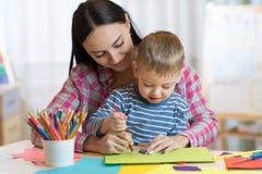 Disegno della donna dell'insegnante con il ragazzo del bambino in aula immagine stock