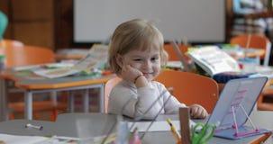 Disegno della ragazza alla tavola in aula Istruzione Bambino che si siede ad uno scrittorio stock footage
