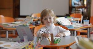 Disegno della ragazza alla tavola in aula Istruzione Bambino che si siede ad uno scrittorio fotografia stock libera da diritti