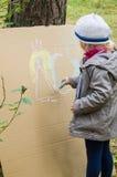 Disegno della ragazza con i pastelli su cartone Fotografia Stock