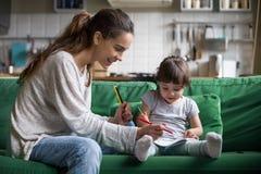Disegno della ragazza del bambino e della mamma con le matite colorate a casa fotografia stock