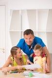 Disegno e pittura felici adorabili della famiglia a casa Fotografia Stock