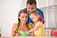 Disegno e pittura felici adorabili della famiglia a casa Fotografie Stock