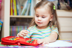 Disegno felice della bambina con le matite fotografia stock