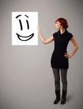 Disegno sorridente del fronte della tenuta della giovane donna Immagine Stock Libera da Diritti