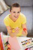 Disegno sorridente della giovane donna sull'uovo di rosso di Pasqua Fotografie Stock Libere da Diritti