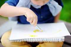 Disegno sveglio del ragazzino con le pitture variopinte nel parco di estate Immagini Stock Libere da Diritti