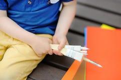Disegno sveglio del ragazzino con le pitture variopinte nel parco di estate Fotografia Stock