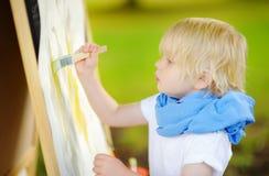 Disegno sveglio del ragazzino con le pitture variopinte nel parco di estate Immagine Stock