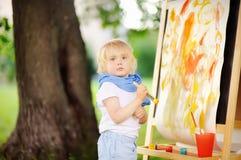 Disegno sveglio del ragazzino con le pitture variopinte nel parco di estate Fotografia Stock Libera da Diritti