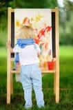 Disegno sveglio del ragazzino con le pitture variopinte nel parco di estate Immagini Stock