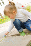 Disegno sveglio della bambina con il gesso blu Fotografie Stock